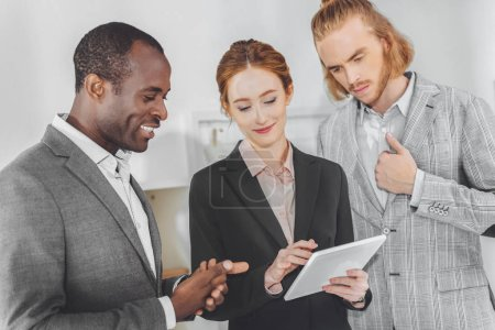 multicultural businesspeople looking at tablet in office