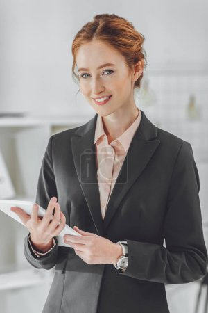 smiling businesswoman holding tablet and looking at camera