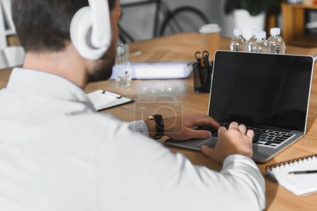 handsome businessman listening music and working at laptop