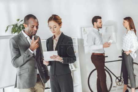 multicultural businesspeople discussing something on office