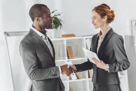 Photo pour Homme d'affaires américain africain et femme d'affaires caucasienne, serrant la main - image libre de droit