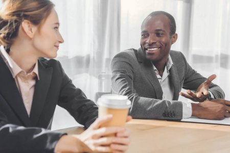 african man smiling to woman with coffe in hands  at office space