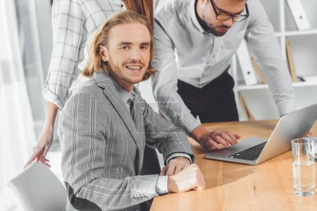 Photo for Man smiling to camera while other people looking at laptop on table - Royalty Free Image