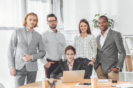 business team standing against sitting woman at office space