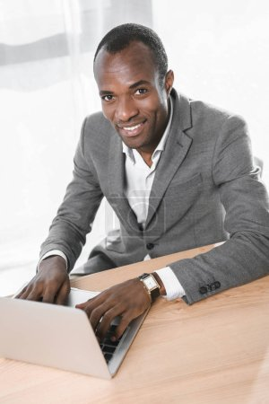 smiling african man looking at camera while using laptop on table