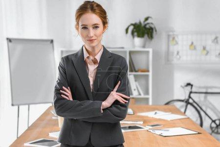 Photo pour Femme d'affaires avec les bras croisés en regardant la caméra à l'espace de bureau - image libre de droit