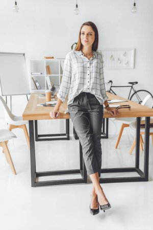 woman in shirt leaning on table and looking away at office space