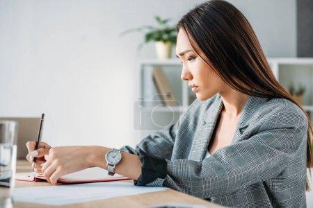 Photo pour Vue latérale de sérieux attrayant asiatique femme d'affaires écrit quelque chose à portable dans le bureau - image libre de droit