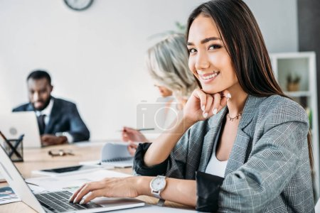 Photo for Smiling attractive asian businesswoman using laptop and looking at camera in office - Royalty Free Image