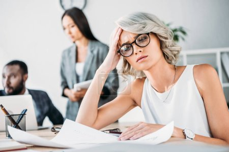 exhausted caucasian businesswoman sitting at table in office and looking at documents