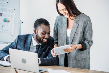 smiling african american businessman and asian businesswoman looking at tablet in office