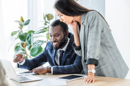 smiling african american businessman pointing on something at laptop to asian businesswoman
