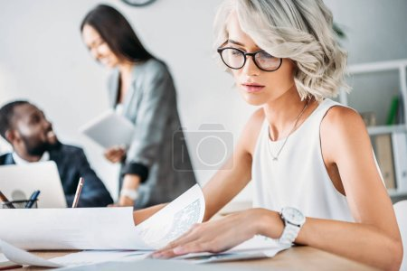 attractive young caucasian businesswoman reading documents in office