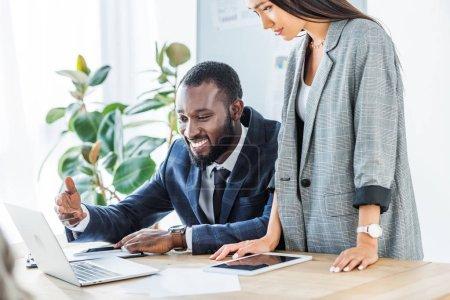 Photo pour Sourire, homme d'affaires américain africain et asiatique femme regardant ordinateur portable au bureau - image libre de droit