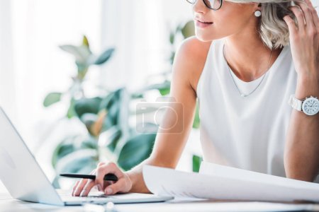 Photo for Cropped image of businesswoman using laptop in office - Royalty Free Image