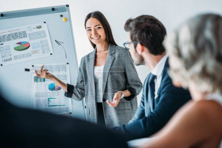 smiling asian businesswoman pointing on flipchart during meeting in office