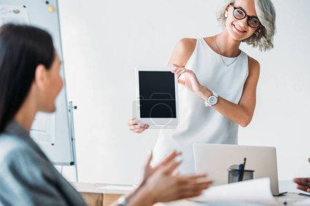 smiling businesswoman showing tablet with blank screen to colleague in office