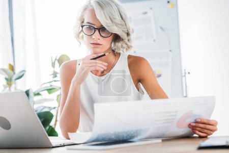 Photo pour Belle femme d'affaires caucasien travaillant au cabinet avec des documents et ordinateur portable - image libre de droit