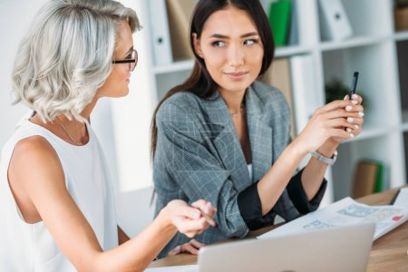 caucasian businesswoman pointing on something at laptop to asian colleague in office