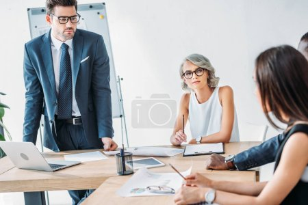 Photo for Young multicultural businesspeople sitting at table during meeting in office - Royalty Free Image