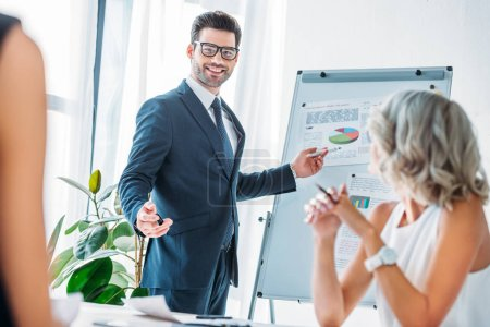 smiling businessman pointing on flipchart during presentation in office