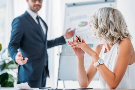 cropped image of businessman gesturing while standing near flipchart in office
