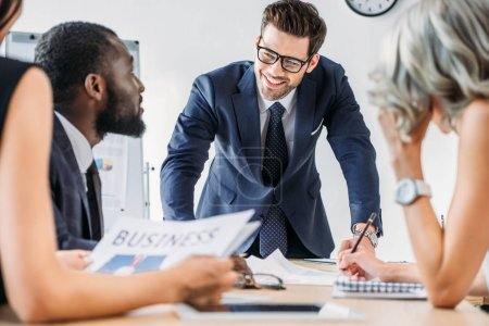 young multiethnic businesspeople sitting at table during meeting in office