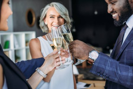smiling multiethnic businesspeople clinking with glasses of champagne in office