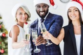 multiethnic businesspeople in santa hats clinking with glasses of champagne in office and looking at camera