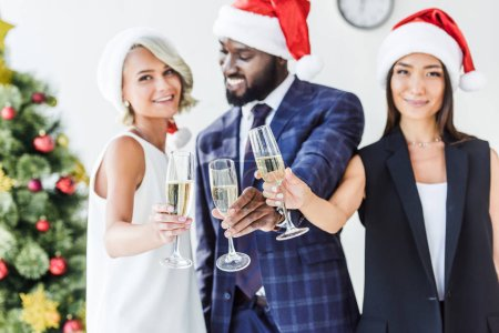Photo for Selective focus of multiethnic businesspeople in santa hats clinking with glasses of champagne in office - Royalty Free Image