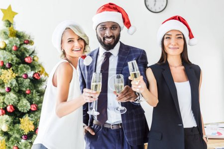 Photo for Happy multiethnic businesspeople in santa hats holding glasses of champagne in office - Royalty Free Image