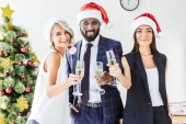 happy multiethnic businesspeople in santa hats holding glasses of champagne in office