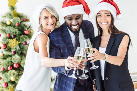 Photo for Happy multiethnic businesspeople in santa hats clinking with glasses of champagne in office - Royalty Free Image