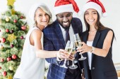 happy multiethnic businesspeople in santa hats clinking with glasses of champagne in office