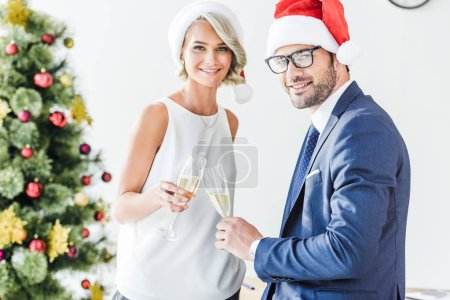 smiling businesspeople in santa hats clinking with glasses of champagne in office