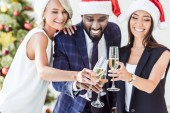 smiling multiethnic businesspeople in santa hats clinking with glasses of champagne in office