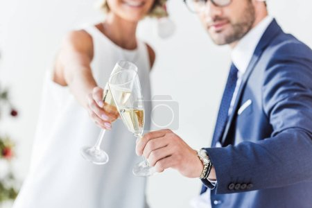 Photo for Cropped image of businesspeople in santa hats clinking with glasses of champagne in office - Royalty Free Image