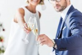 cropped image of businesspeople in santa hats clinking with glasses of champagne in office