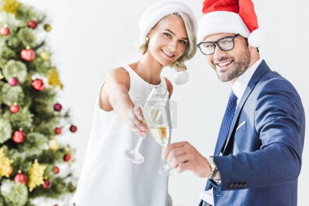 Photo for Young businesspeople in santa hats clinking with glasses of champagne in office - Royalty Free Image