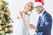 young businesspeople in santa hats clinking with glasses of champagne in office