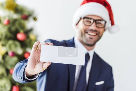 Photo for Smiling businessman in santa hat holding blank card in office with blurred christmas tree on background - Royalty Free Image