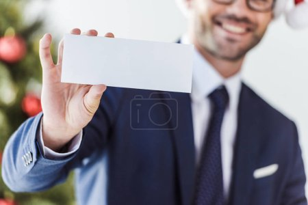 Photo for Cropped image of businessman holding blank card in office with blurred christmas tree on background - Royalty Free Image