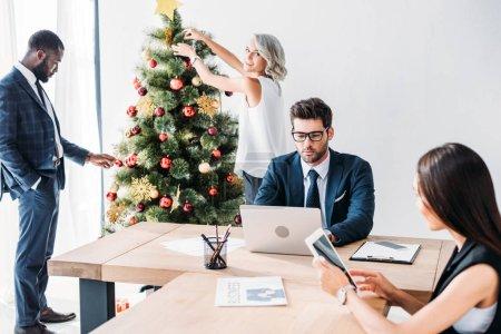 jeunes hommes d'affaires multiculturelles travaillant et décorer le sapin de Noël au bureau