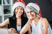 smiling multicultural businesswomen in santa hats looking at camera in office