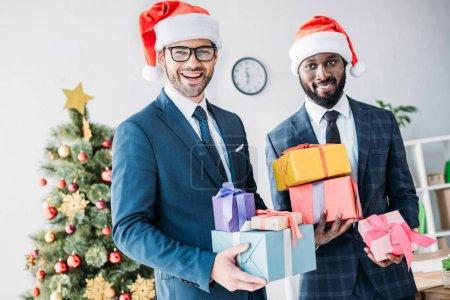 Photo pour Souriants hommes d'affaires multiculturels dans des chapeaux Santa tenant des boîtes-cadeaux dans le bureau - image libre de droit