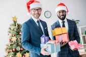 smiling multicultural businessmen in santa hats holding gift boxes in office