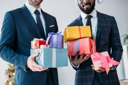 Photo for Cropped image of smiling multicultural businessmen holding gift boxes in office - Royalty Free Image