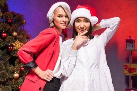 Photo pour Femmes d'affaires multiethniques chapeaux santa regardant la caméra à entreprise fête de nouvel an - image libre de droit
