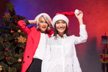 Photo for Happy multicultural businesswomen holding santa hats in office at new year corporate party - Royalty Free Image