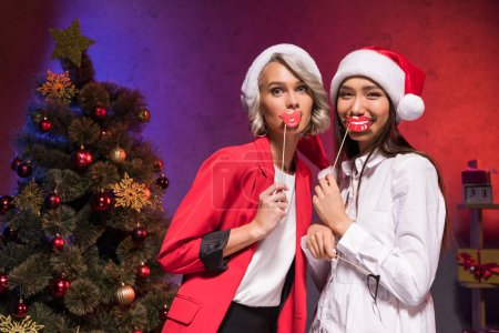 attractive multicultural businesswomen holding fake lips on sticks at new year corporate party